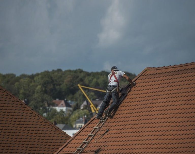 Man doing roof repair on a two story home. Picture taken in Honolulu, HI.