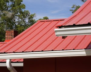 Red metal roofing on a home in Oahu with gutters.