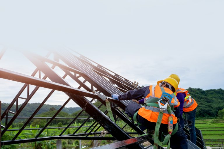 Men in safety gear working on a roof installation.